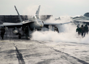 1280px-US_Navy_031203-N-9742R-002_As_steam_from_a_previous_launch_billows_out_of_the_catapult_track,_flight_deck_personnel_hustle_to_prepare_an_F-A-18_Hornet